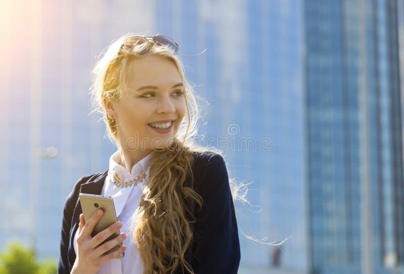 Trabajo ejecutivo con el teléfono móvil en la calle con los edificios de oficinas en el fondo foto de archivo