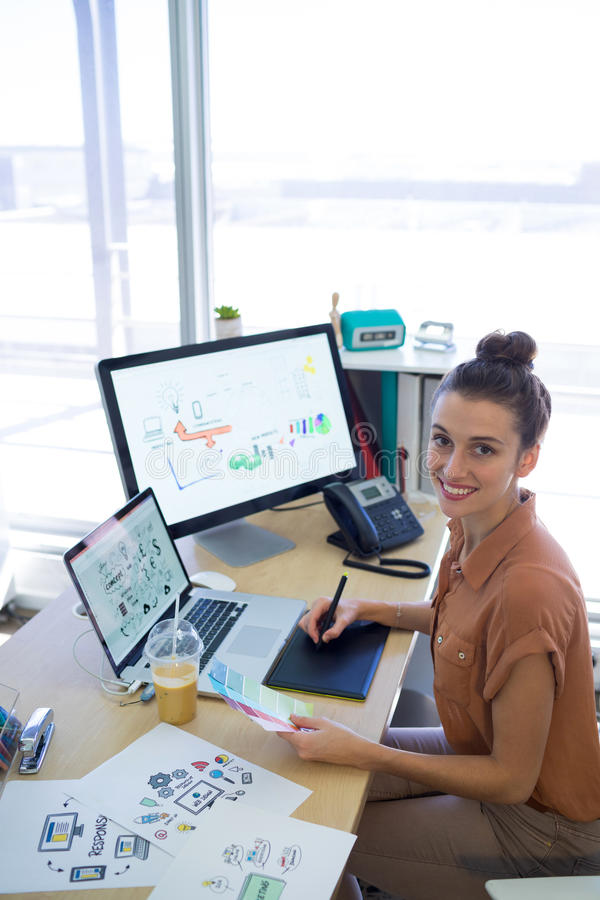 Trabajo ejecutivo femenino sobre la tableta gráfica en su escritorio foto de archivo libre de regalías