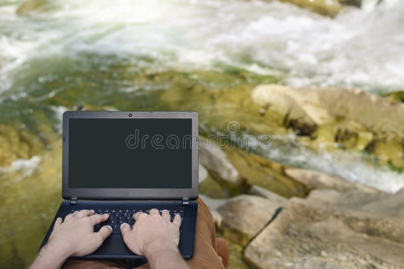 Trabajo en concepto de la naturaleza Las manos de los hombres en el teclado del ordenador portátil en el fondo de un río de la mo fotografía de archivo