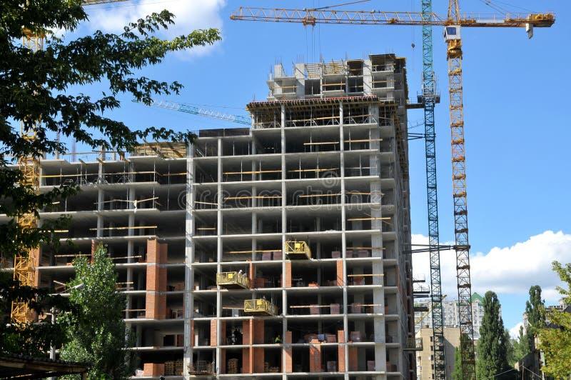 Trabajo en el edificio alto del lugar debajo de la construcción y de grúas debajo fotos de archivo