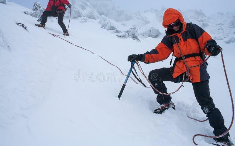 Trabajo en equipo en alpinismo mountaineering Atraviese de la montaña fotos de archivo