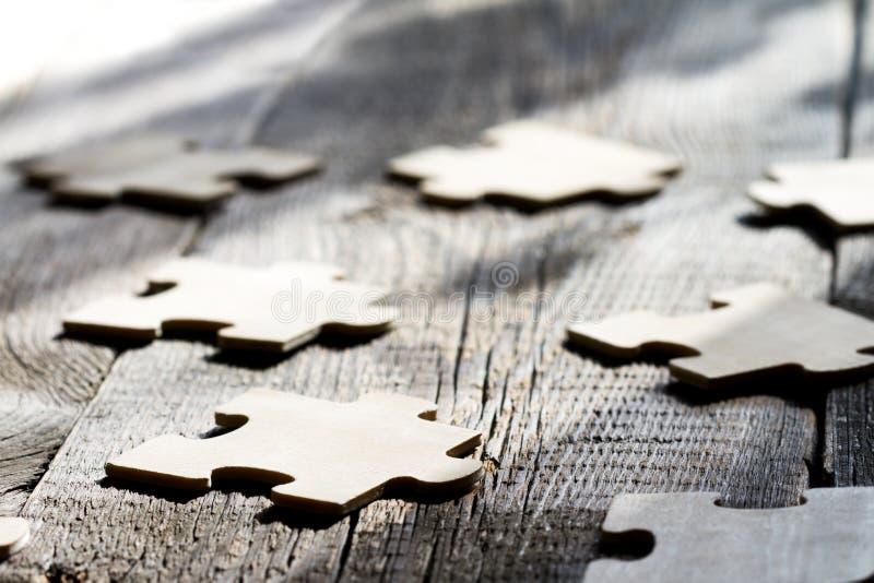 Trabajo en equipo en concepto del extracto del negocio con rompecabezas en el tablero de madera imágenes de archivo libres de regalías
