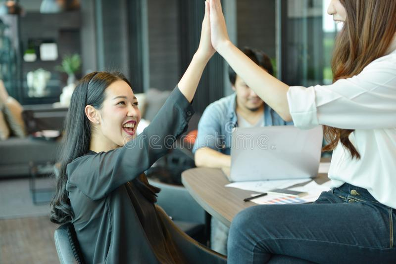 Trabajo en equipo de los hombres de negocios asiáticos que dan el alto cinco, equipo de la etiqueta fotos de archivo libres de regalías