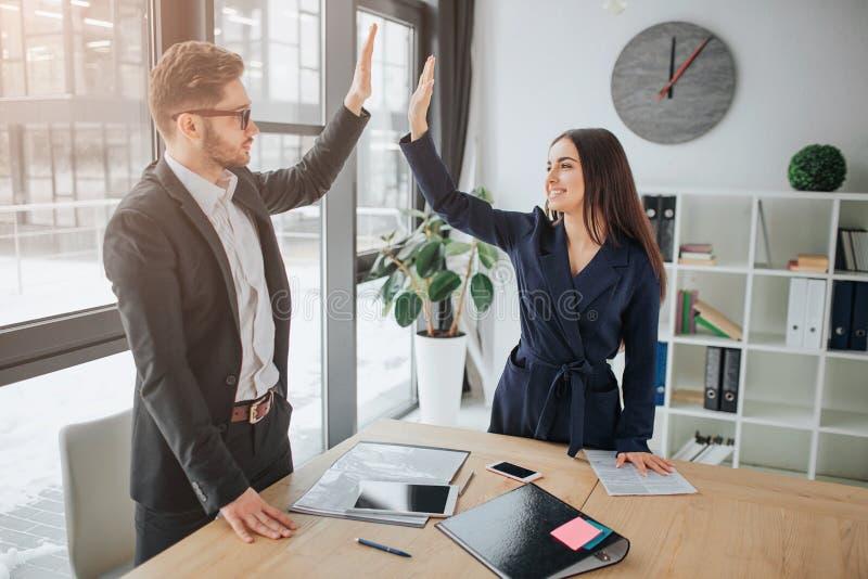 Trabajo en equipo del hombre joven y de la mujer Se colocan en sitio y dan alto-cinco el uno al otro Sonrisa de la gente Parecen  imagen de archivo libre de regalías