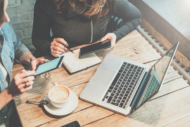 Trabajo en equipo Dos empresarias jovenes que se sientan en la tabla en la cafetería, mirada en su pantalla del smartphone y disc fotografía de archivo libre de regalías