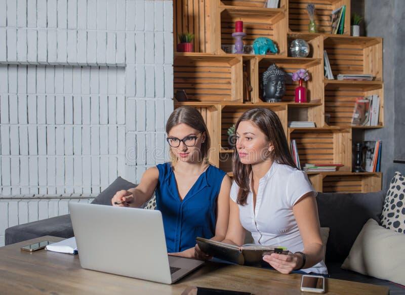 Trabajo en equipo experto de la empresaria dos así como el ordenador portátil, sentándose en espacio de co-trabajo fotografía de archivo libre de regalías