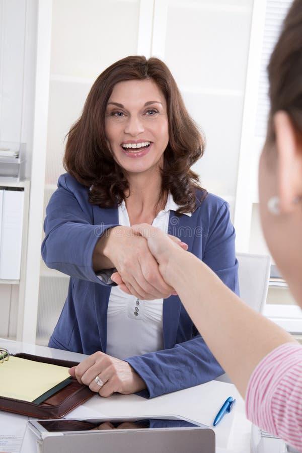 Trabajo en equipo feliz: mujer dos que hace el apretón de manos. imagen de archivo libre de regalías
