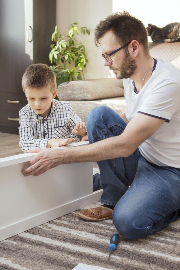Trabajo en equipo en la alfombra en la sala de estar El hombre da vuelta a los muebles El muchacho ayuda en el trabajo imagenes de archivo