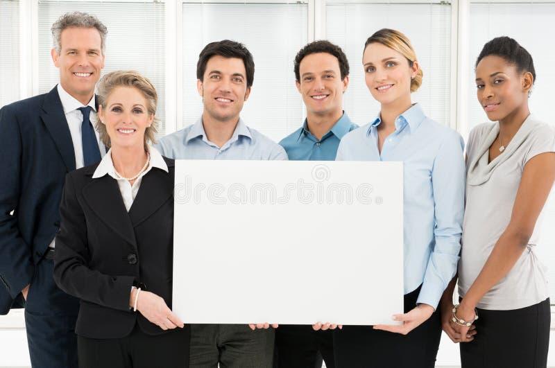 Trabajo en equipo sonriente que celebra la muestra en blanco fotos de archivo