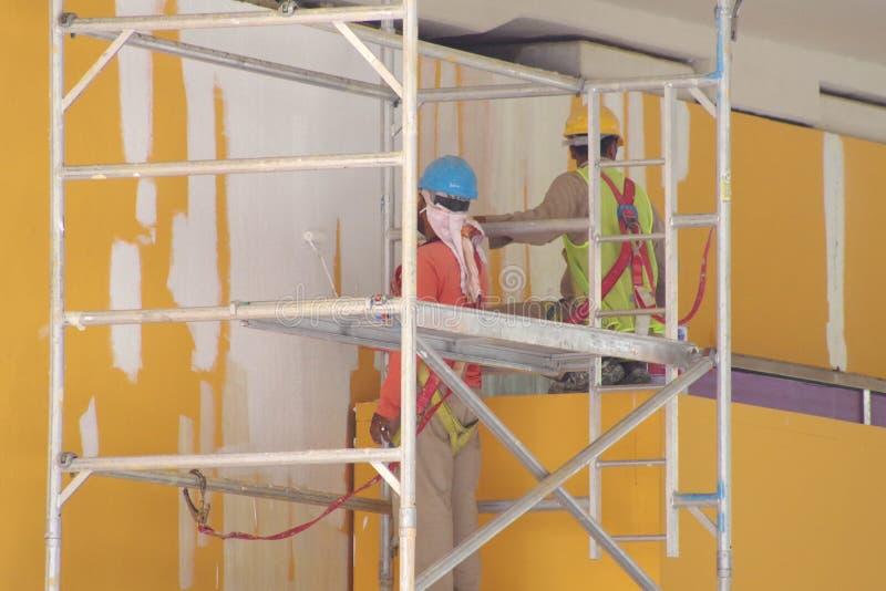 Trabajo en la altura, pintores en la acción en un andamio con el PPE lleno y arnés fotografía de archivo libre de regalías