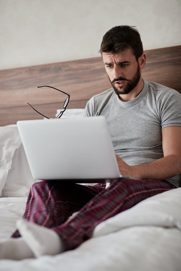 Trabajo en la habitación hombre de negocios que usa el ordenador portátil mientras que s imagenes de archivo