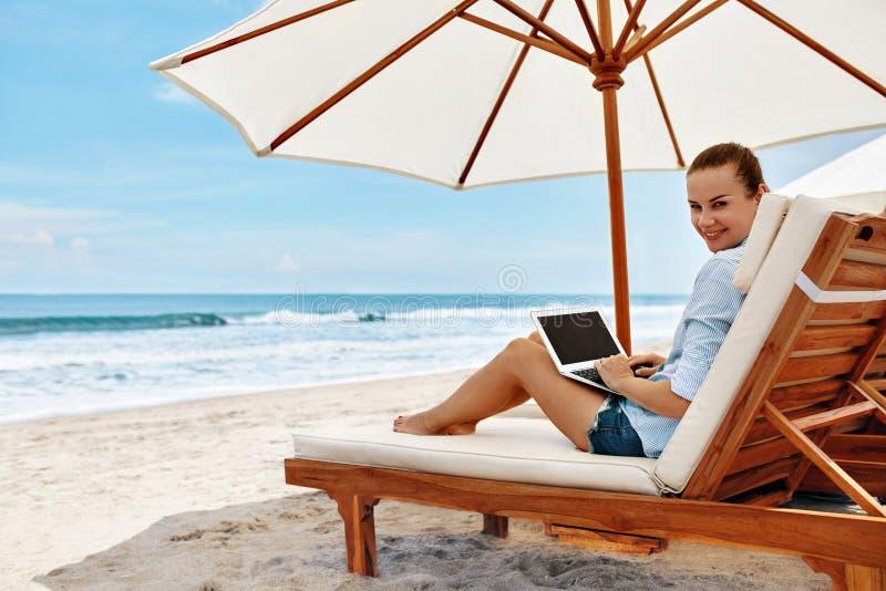 Trabajo en la playa Mujer de negocios que trabaja en línea en el ordenador portátil al aire libre imagen de archivo libre de regalías
