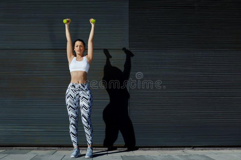 trabajo femenino atractivo en sus brazos al aire libre fotos de archivo