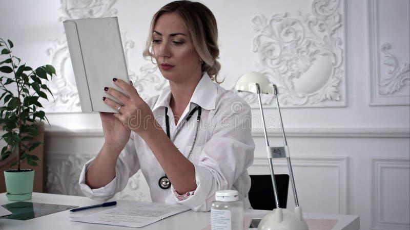 Trabajo femenino joven del doctor sobre la tableta en oficina foto de archivo libre de regalías