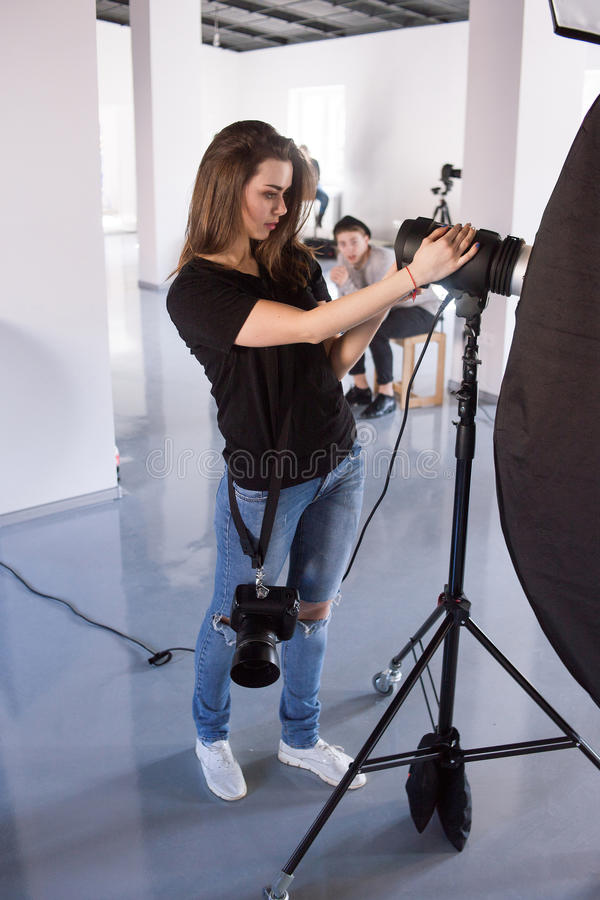 Trabajo femenino joven del fotógrafo en estudio fotografía de archivo