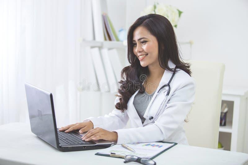 Trabajo femenino sonriente del doctor en su oficina fotos de archivo libres de regalías