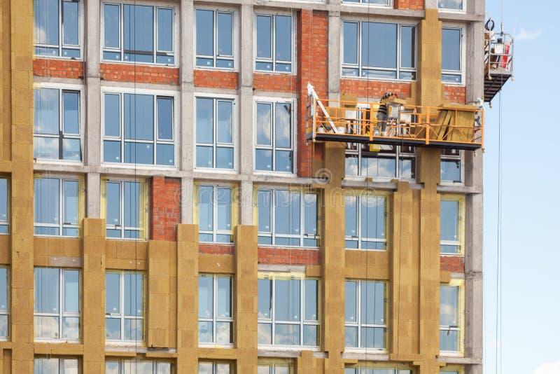 Trabajo a gran altitud sobre las paredes externas del edificio alto Aislamiento de las lanas de cristal El trabajador aísla la ca imagen de archivo libre de regalías