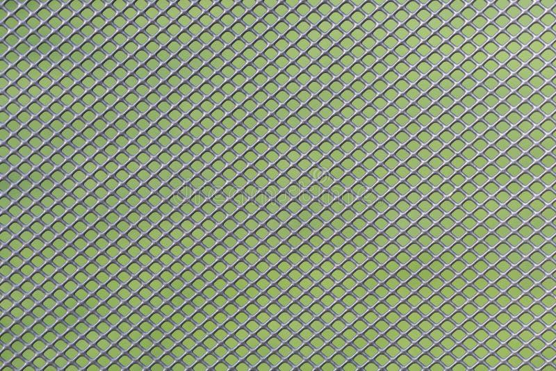 Trabajo gris de la malla de alambre del metal contra un fondo verde foto de archivo libre de regalías