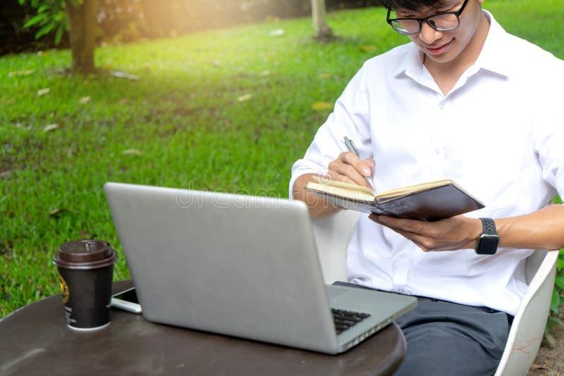 trabajo joven del hombre del buseness sobre la tabla con su ordenador port?til imagenes de archivo