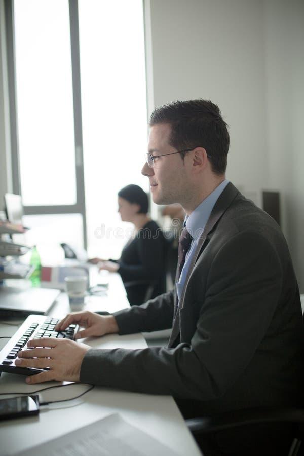 Trabajo joven feliz del hombre de negocios en oficina moderna Hombre de negocios hermoso In Office Bussinesmen reales del economi imagen de archivo