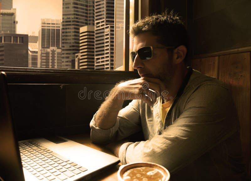 Trabajo joven feliz y acertado atractivo joven del hombre de negocios relajado de cafetería de Internet con el ordenador portátil imagen de archivo libre de regalías