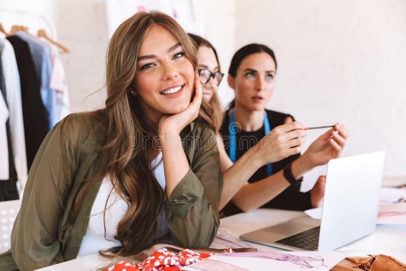 Trabajo lindo de tres de las mujeres jovenes diseñadores de ropa fotografía de archivo