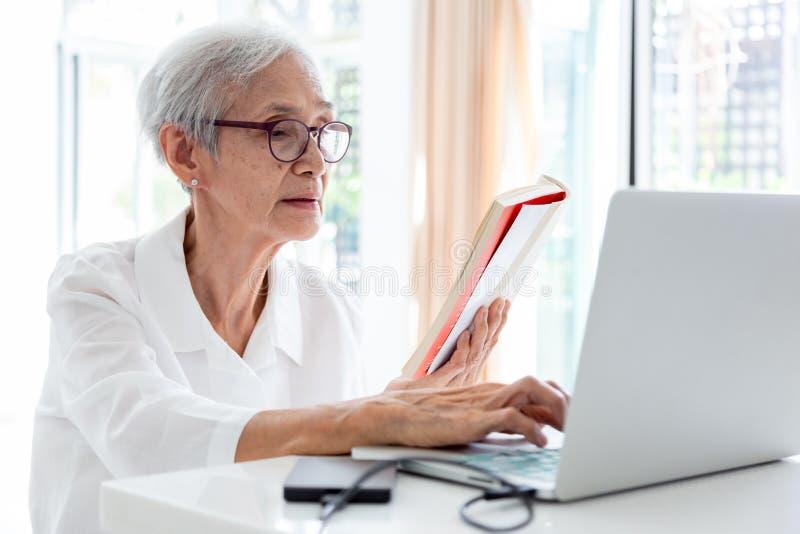 Trabajo mayor asi?tico feliz de la mujer, practicando surf Internet con el ordenador port?til en la tabla en hogar, personas mayo fotos de archivo