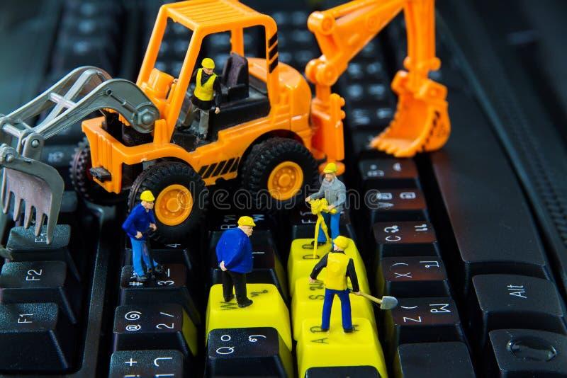 Trabajo minúsculo de la reparación de los trabajadores de los juguetes sobre el teclado de ordenador imagen de archivo