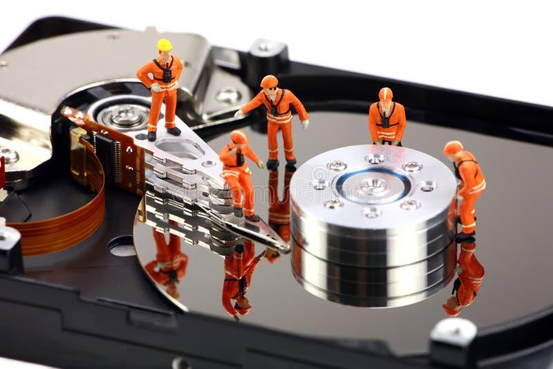Trabajo miniatura de los técnicos sobre mecanismo impulsor duro fotos de archivo libres de regalías
