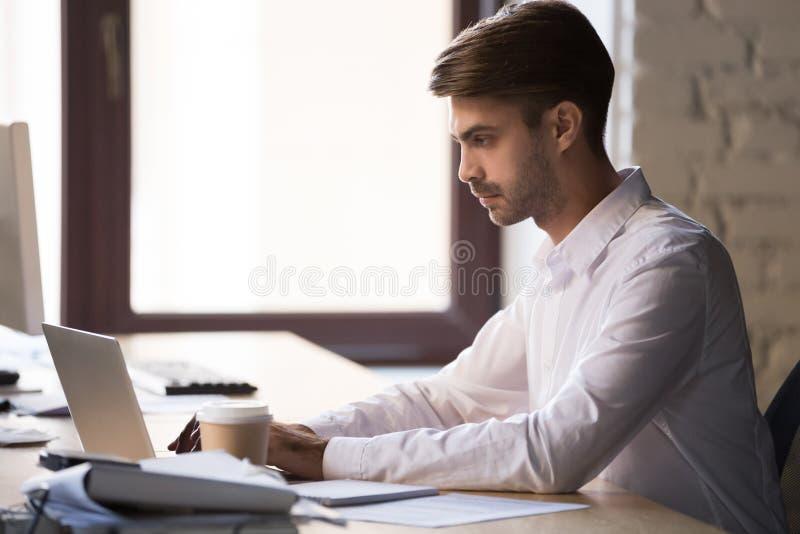 Trabajo ocupado enfocado del empleado de sexo masculino en el ordenador portátil en oficina foto de archivo libre de regalías