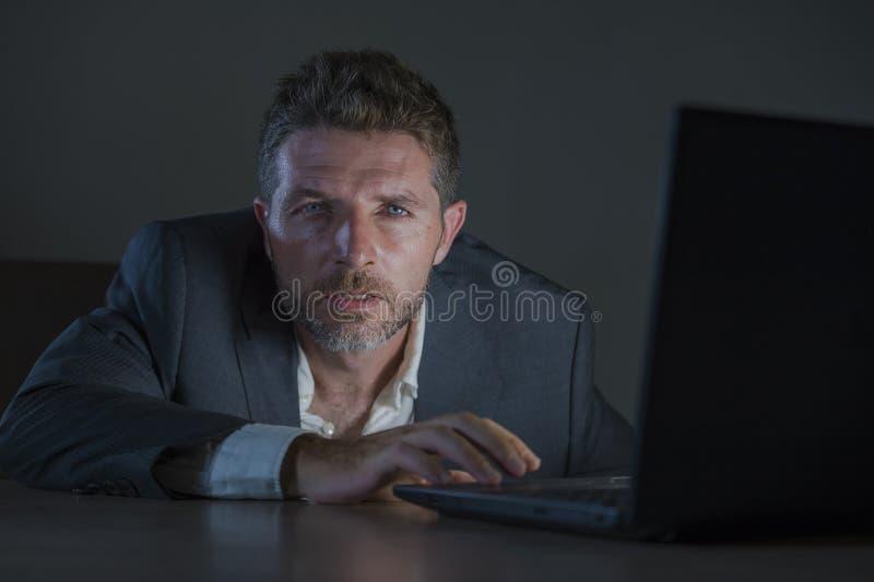 Trabajo perdido y cansado atractivo del hombre del empresario de última hora en el escritorio del ordenador portátil de la oficin fotos de archivo libres de regalías