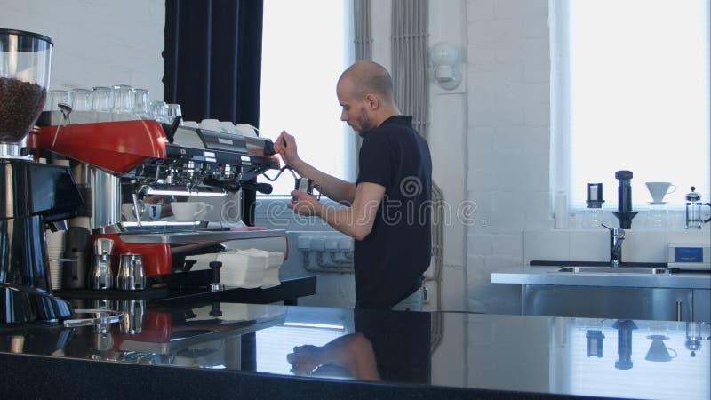 Trabajo profesional del barista, preparando la leche para el café fotos de archivo