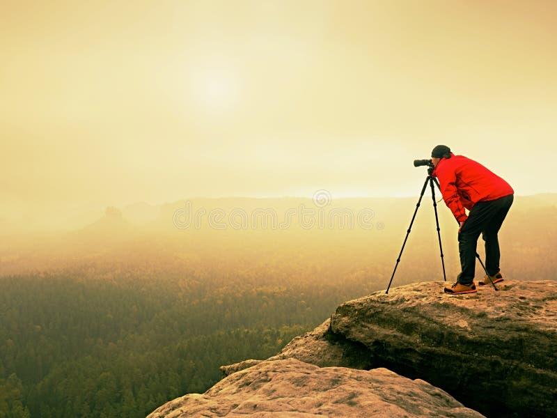 Trabajo profesional del fotógrafo sobre pico de montaña El fotógrafo de la naturaleza toma las fotos con la cámara del espejo en  fotografía de archivo libre de regalías
