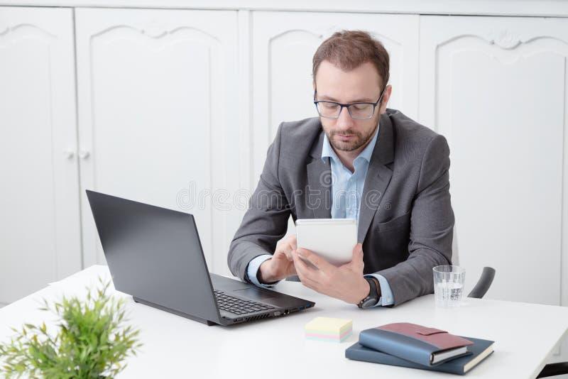 Trabajo profesional joven en el dispositivo digital de la tableta en el escritorio foto de archivo