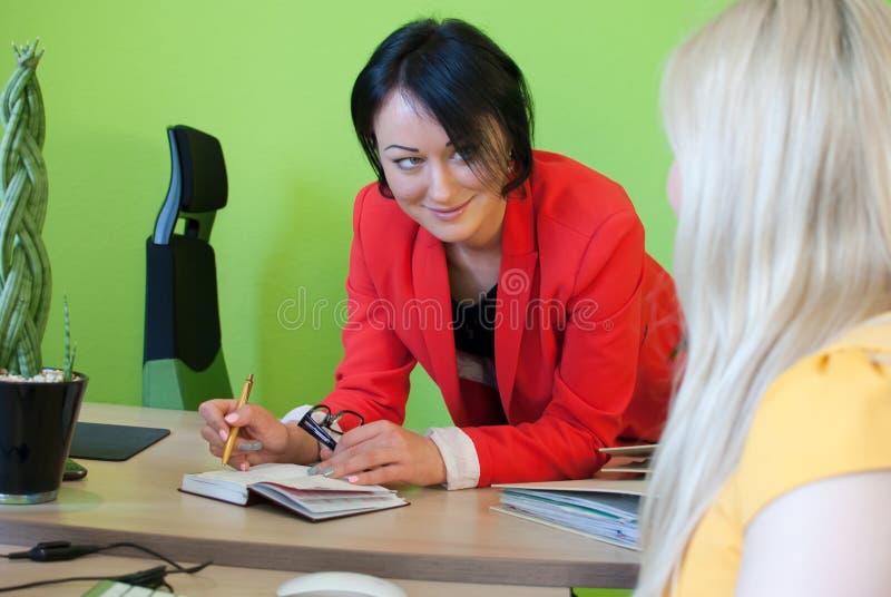 Trabajo que habla de la mujer dos del diálogo del negocio de la oficina imagen de archivo