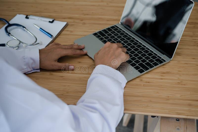 Trabajo que se sienta del doctor joven con el ordenador portátil en el escritorio fotos de archivo