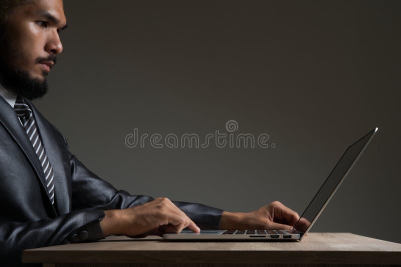 Trabajo que se sienta del hombre de negocios joven con el ordenador portátil aislado en negro fotos de archivo libres de regalías