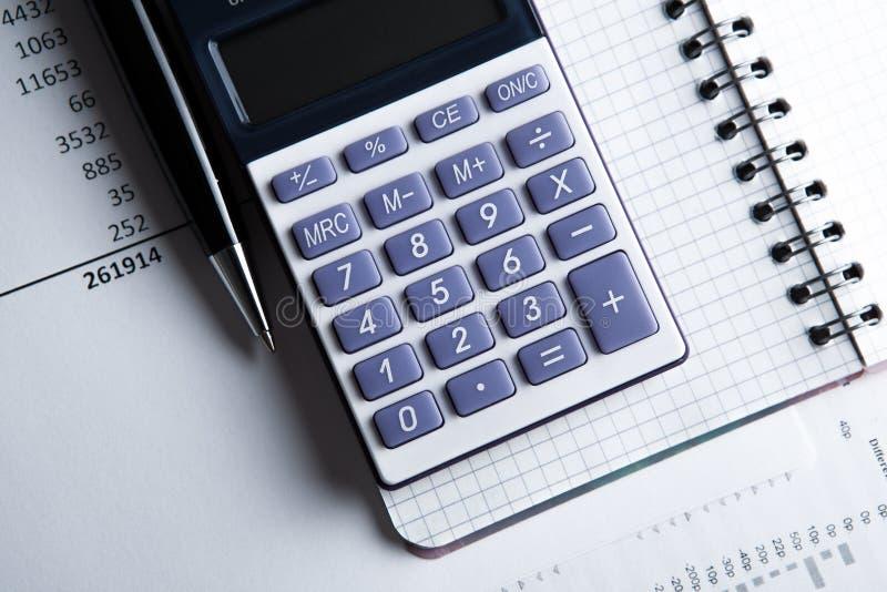 Trabajo sobre la calculadora y los papeles fotos de archivo