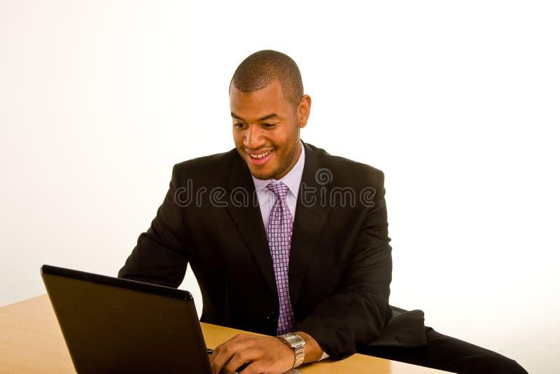 Trabajo sonriente del hombre negro en la computadora portátil foto de archivo libre de regalías