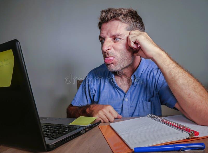 Trabajo subrayado y trastornado loco joven del hombre sucio en gesticular desesperado del escritorio de oficina enojado al ordena foto de archivo