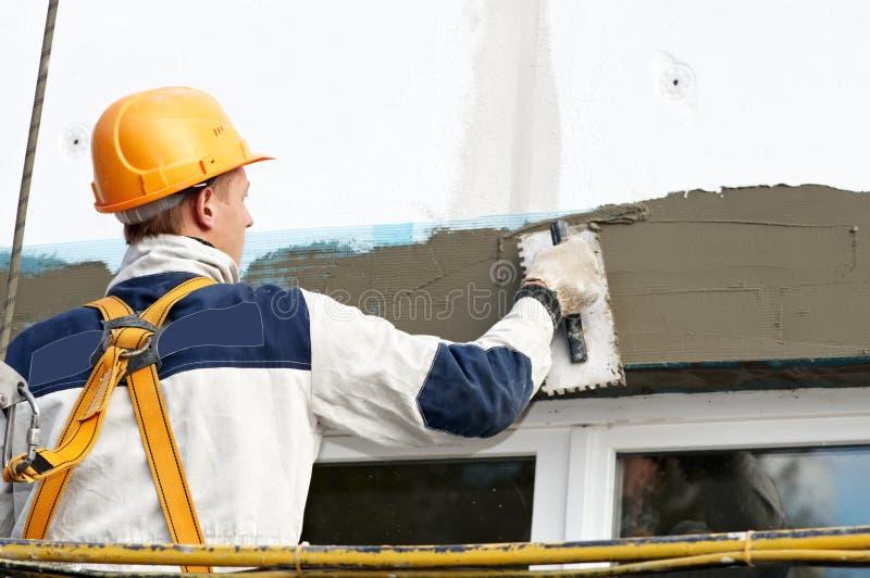 Trabajos de la detención y de la máquina de alisar o cepillar de la fachada imagenes de archivo