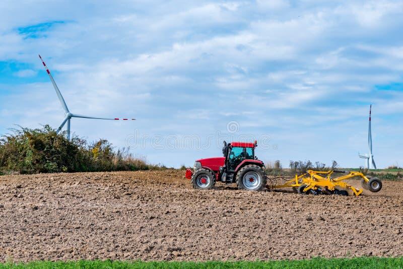 Trabajos en el terreno del otoño cerca de los molinoes de viento fotos de archivo