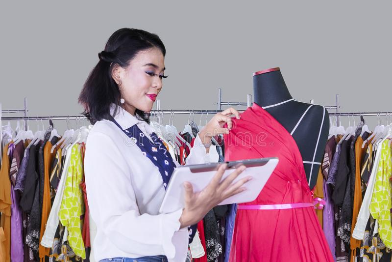 Trabajos femeninos de la modista con la tableta y el maniquí imagenes de archivo