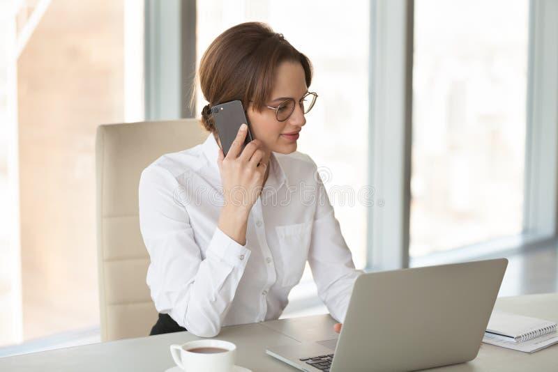 Trabajos múltiple ocupados de la empresaria que hablan en el teléfono y que trabajan en fotos de archivo libres de regalías