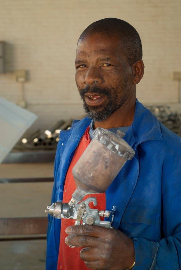 Trabalhador africano com o injetor de pulverizador da pintura imagens de stock