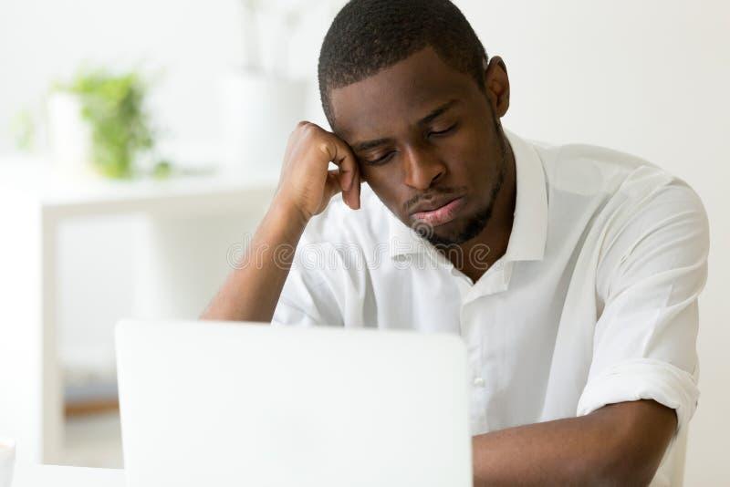 Trabalhador afro-americano cansado que sente sonolento na frente do portátil imagem de stock