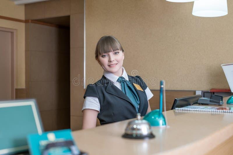 Trabalhador amigável do hotel que levanta atrás da recepção foto de stock royalty free