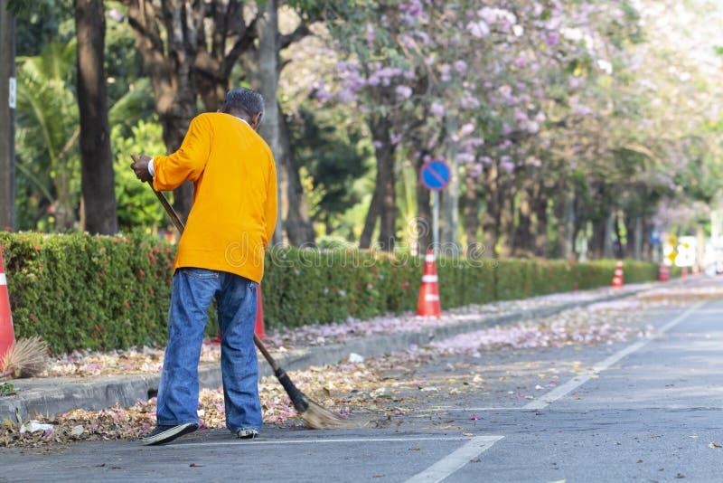 Trabalhador asiático do homem que limpa a estrada fotos de stock