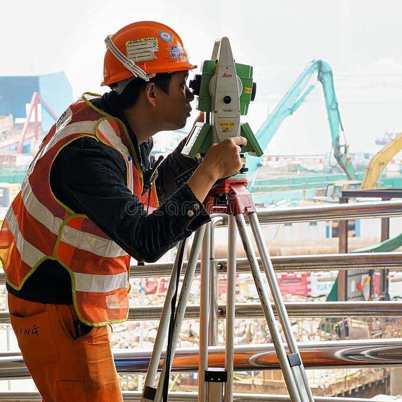 Trabalhador asiático no capacete que faz o trabalho de engenharia em Hong Kong imagem de stock