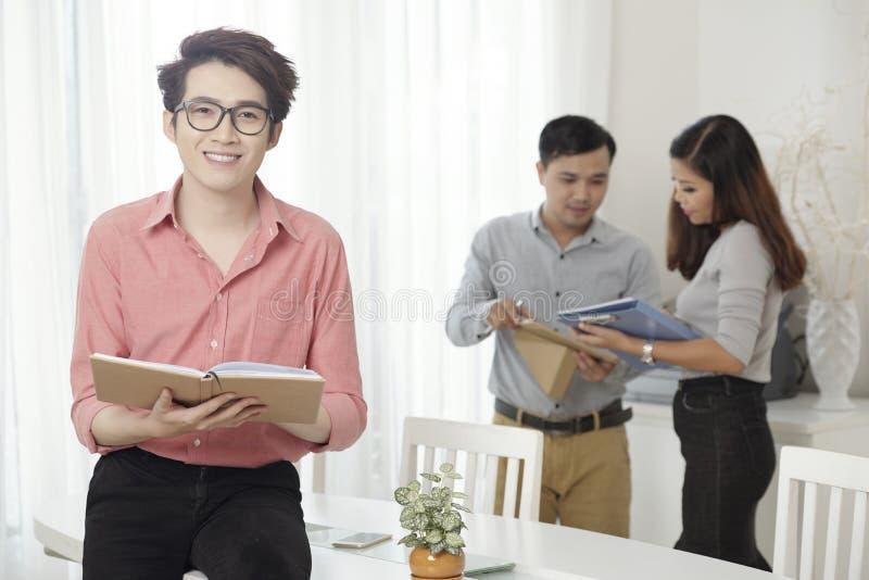 Trabalhador asiático novo com livro e colegas foto de stock royalty free